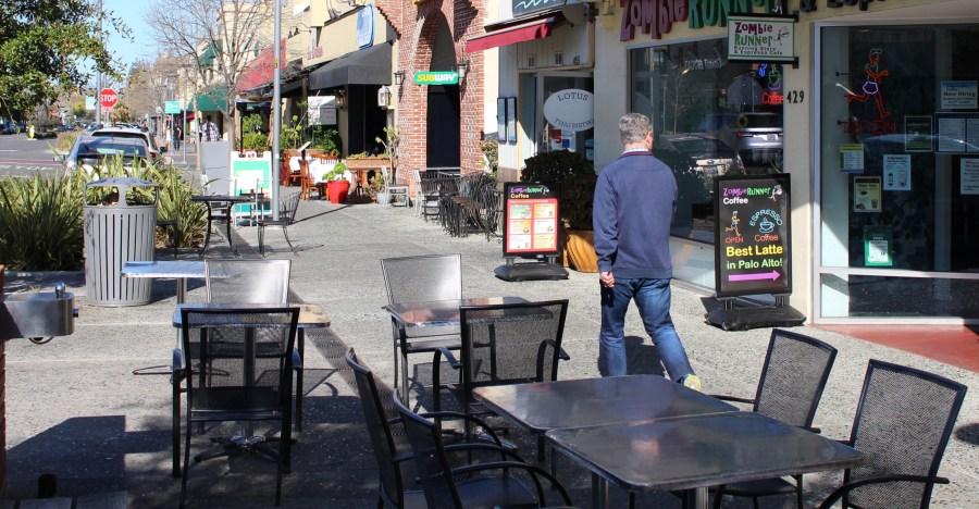 A man glances strides along a quiet sidewalk in downtown Palo Alto in Santa Clara County on March 12, 2020. (GLENN CHAPMAN/AFP via Getty Images)