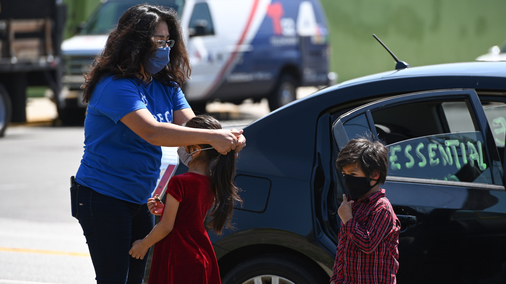 "Activist Michelle Lozano puts a mask on her children Maya, center, and Iker as day laborers and their supporters participate in a ""Caravan for Essential and Excluded Workers'' in Los Angeles on April 14, 2020. (Robyn Beck / AFP / Getty Images)"
