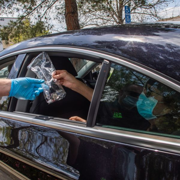 Worshippers are given communion inside their car while Pastor Tim Thompson leads an on-line Sunday Service in the Christian '412 Church Murrieta' parking lot on April 19, 2020 in Murietta, California. (Photo by APU GOMES/AFP via Getty Images)