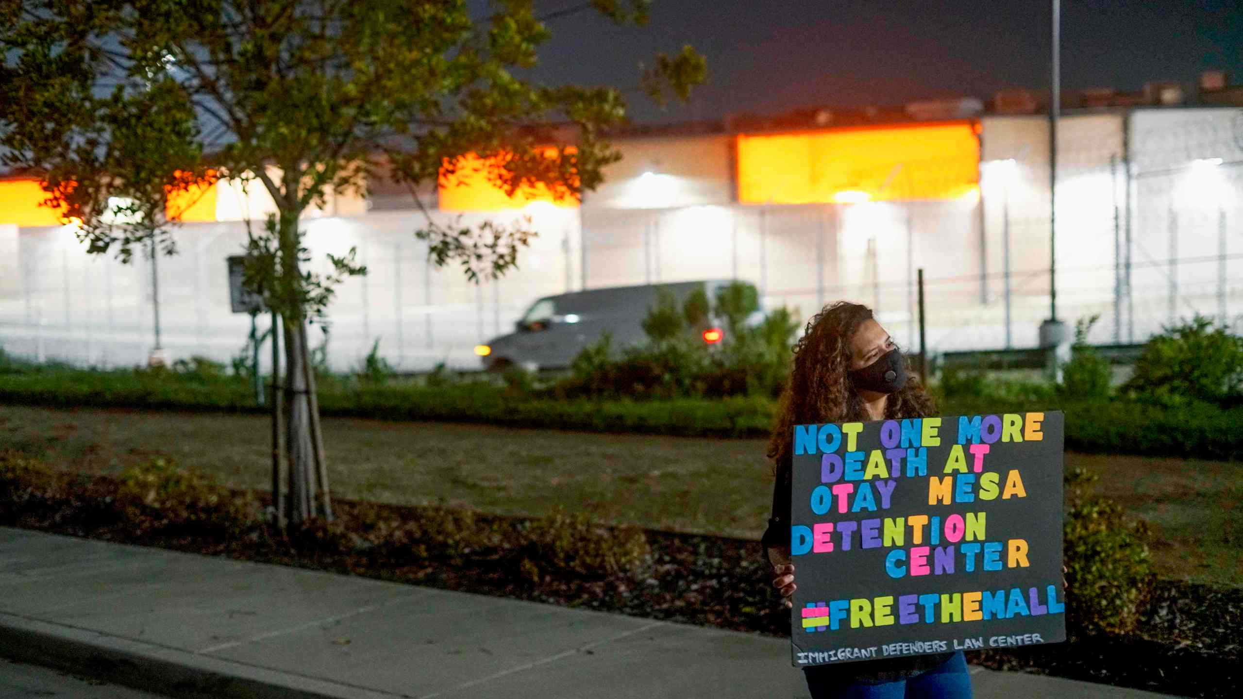 """A Protester stands outside the Otay Mesa Detention Center during a """"Vigil for Carlos"""" rally on May 9, 2020. The vigil was held to commemorate Carlos Ernesto Escobar Mejia, the first immigrant who died of COVID-19 related symptoms while being held at the detention Center. (SANDY HUFFAKER / AFP via Getty Images)"""