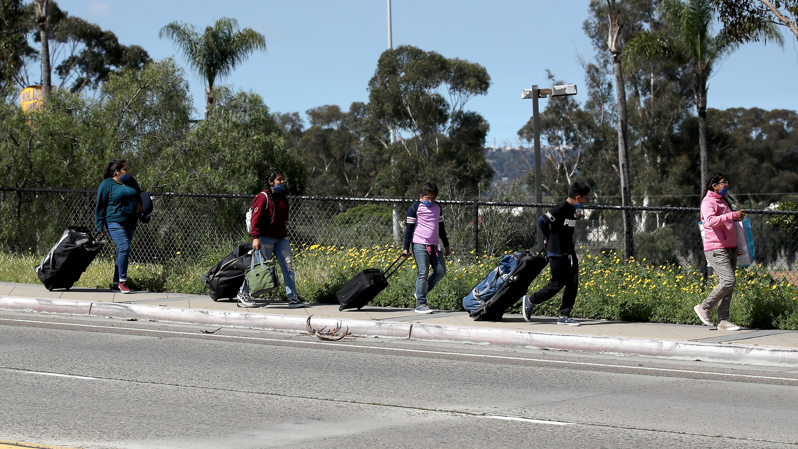 A family walks towards the U.S. Customs and Border Protection at the San Ysidro Port of Entry on March 21, 2020 in San Diego. (Sean M. Haffey/Getty Images)