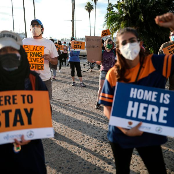 People hold signs during a rally in support of the Supreme Court's ruling in favor of the Deferred Action for Childhood Arrivals (DACA) program, in San Diego on June 18, 2020. (SANDY HUFFAKER/AFP via Getty Images)