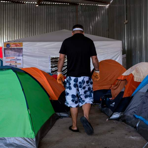 An asylum seeker walks among tents, with one in the background dedicated to people suspected to be infected with COVID-19, at the Juventud 2000 migrant shelter in Tijuana on June 19, 2020. (Guillermo Arias / AFP / Getty Images)
