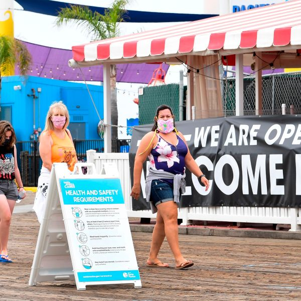 People wearing face masks walk past a health and safety guideline board and an open restaurant on the Santa Monica Pier on June 26, 2020. (FREDERIC J. BROWN/AFP via Getty Images)