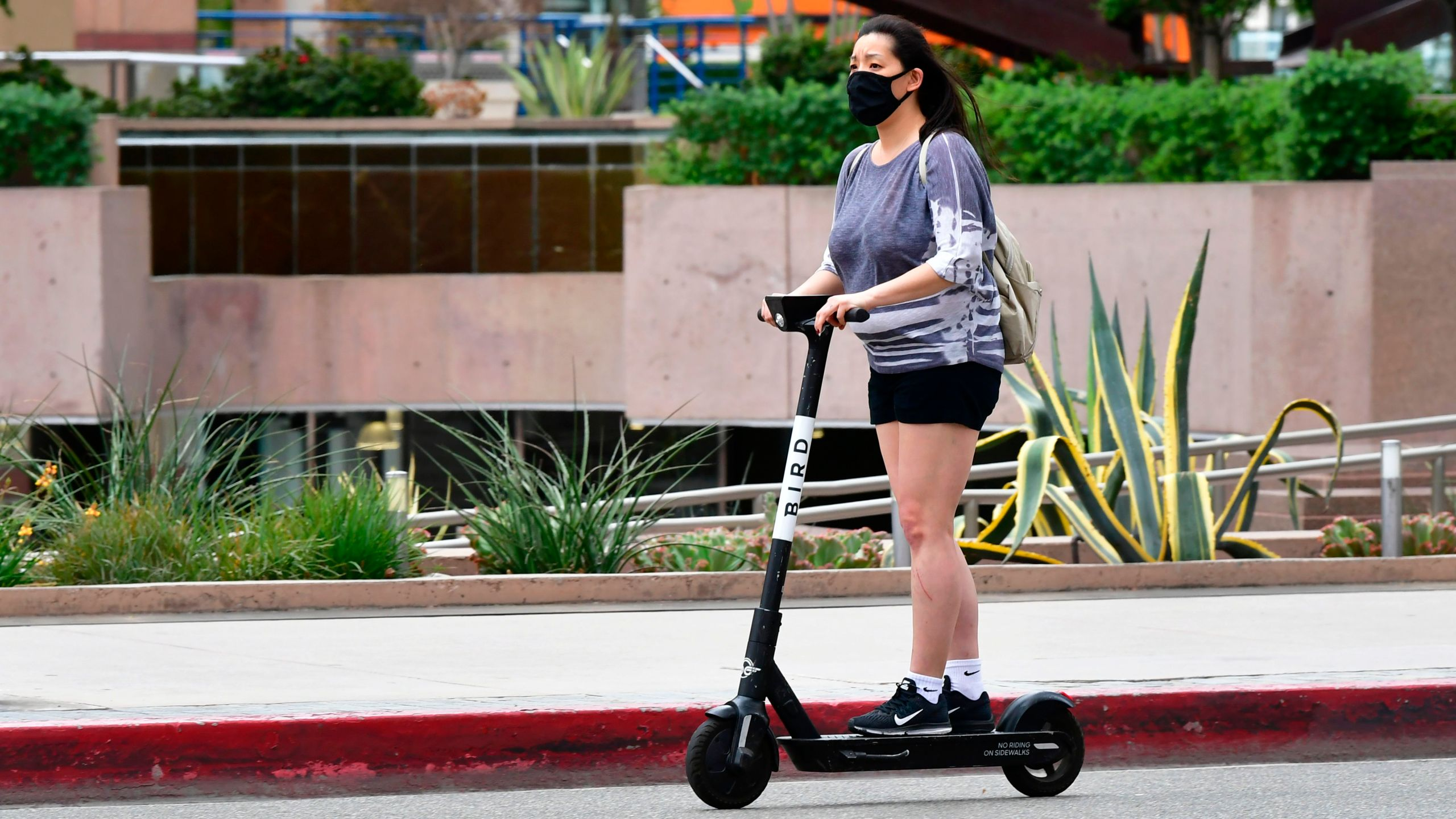 A commuter on electric scooter wears her facemask in Los Angeles on June 29, 2020. (FREDERIC J. BROWN/AFP via Getty Images)