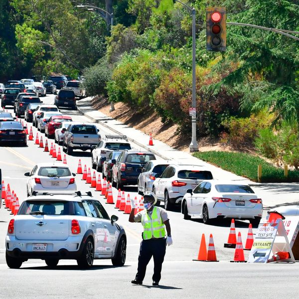 Traffic is directed at Dodger Stadium as people arrive for COVID-19 testing on June 30, 2020. (Frederic J. Brown / AFP / Getty Images)