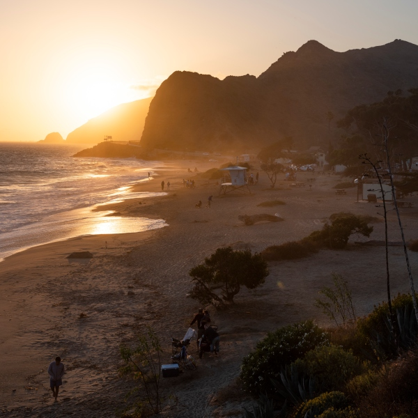 Beachgoers catch the last of the sunset light in the ocean alongside the Pacific Coast Highway on July 2, 2020. (Brent Stirton/Getty Images)