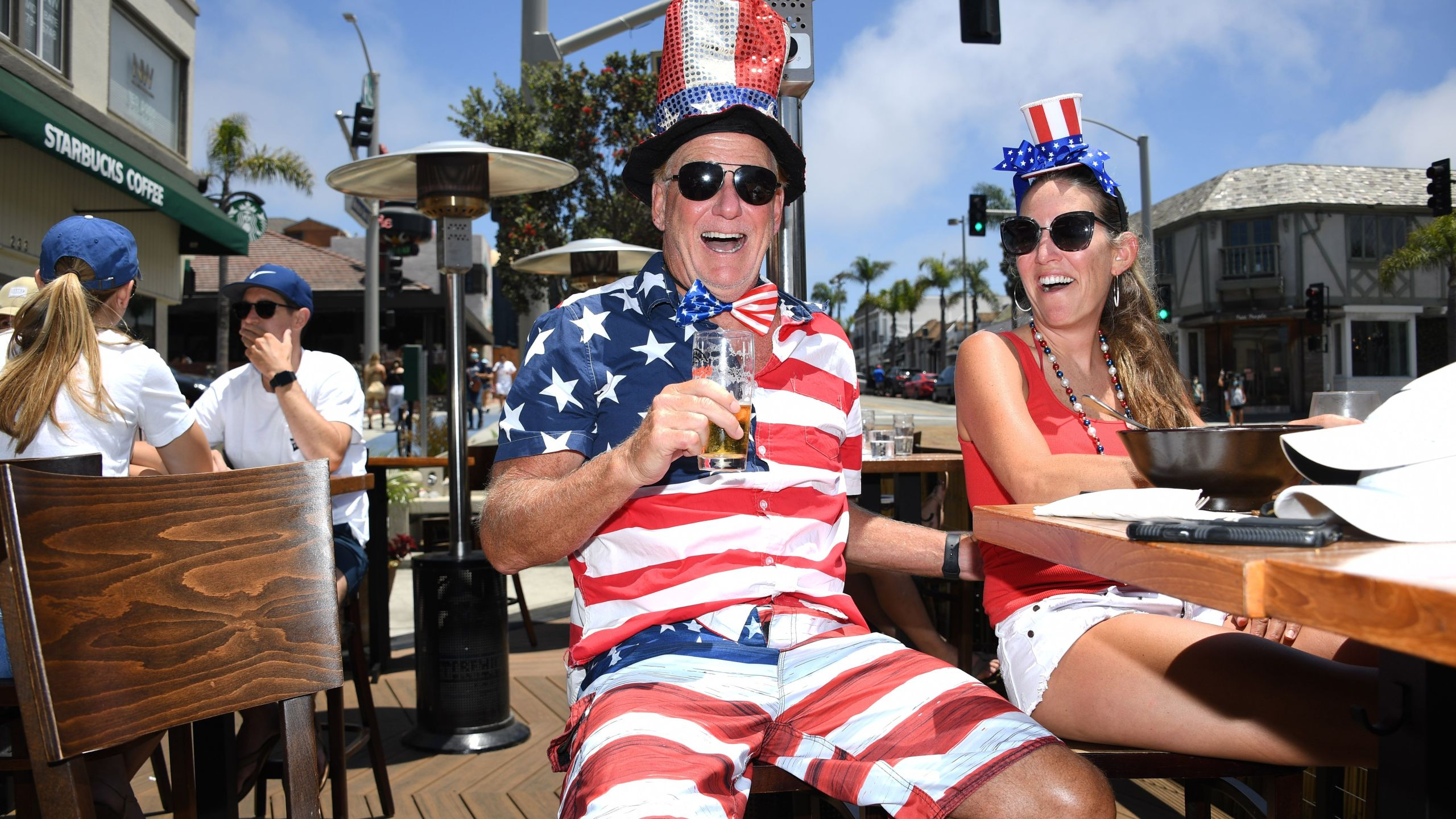 Dave Barnes enjoys a holiday lunch with his wife Christy Barnes at an outdoor restaurant in Manhattan Beach, California where beaches are closed due to a spike in COVID-19 in Los Angeles County, on July 4, 2020, the U.S. Independence Day holiday. (ROBYN BECK/AFP via Getty Images)