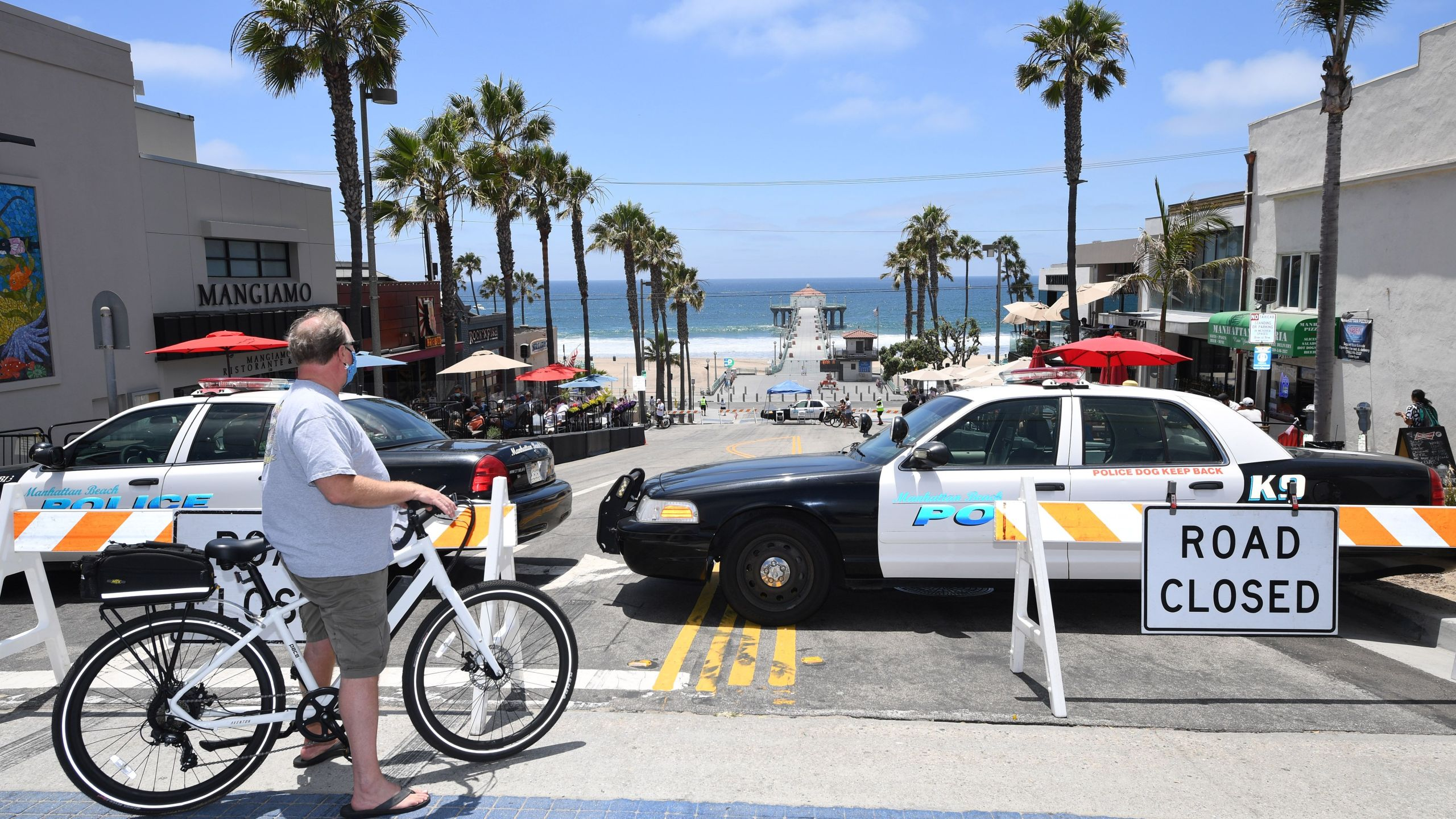 A man wearing a mask looks out over a road closed to traffic near the pier in Manhattan Beach on July 4, 2020. (ROBYN BECK/AFP via Getty Images)