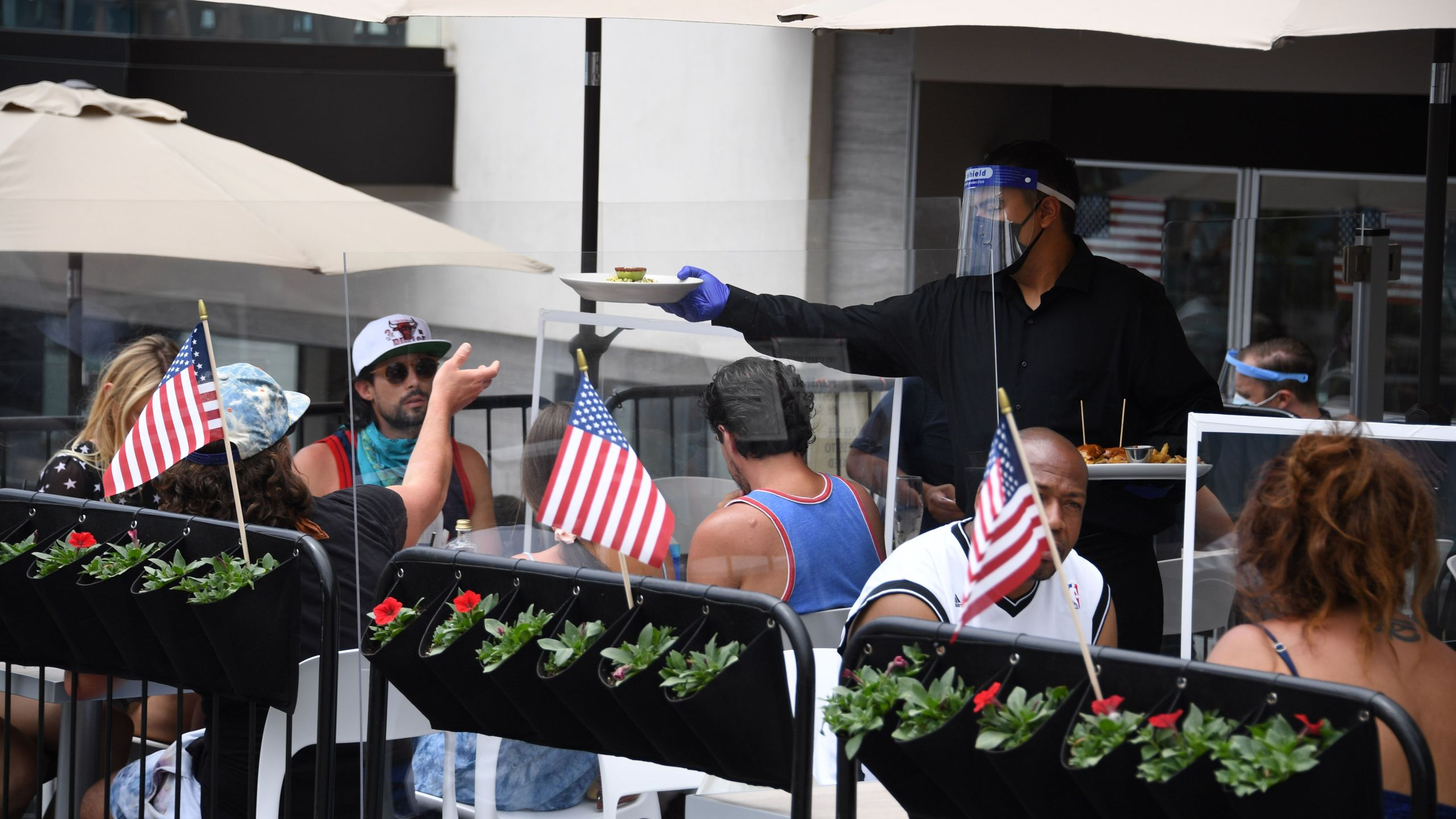 A waiter wearing a face shield serves food on a restaurant patio in Manhattan Beach on July 4, 2020. (ROBYN BECK/AFP via Getty Images)
