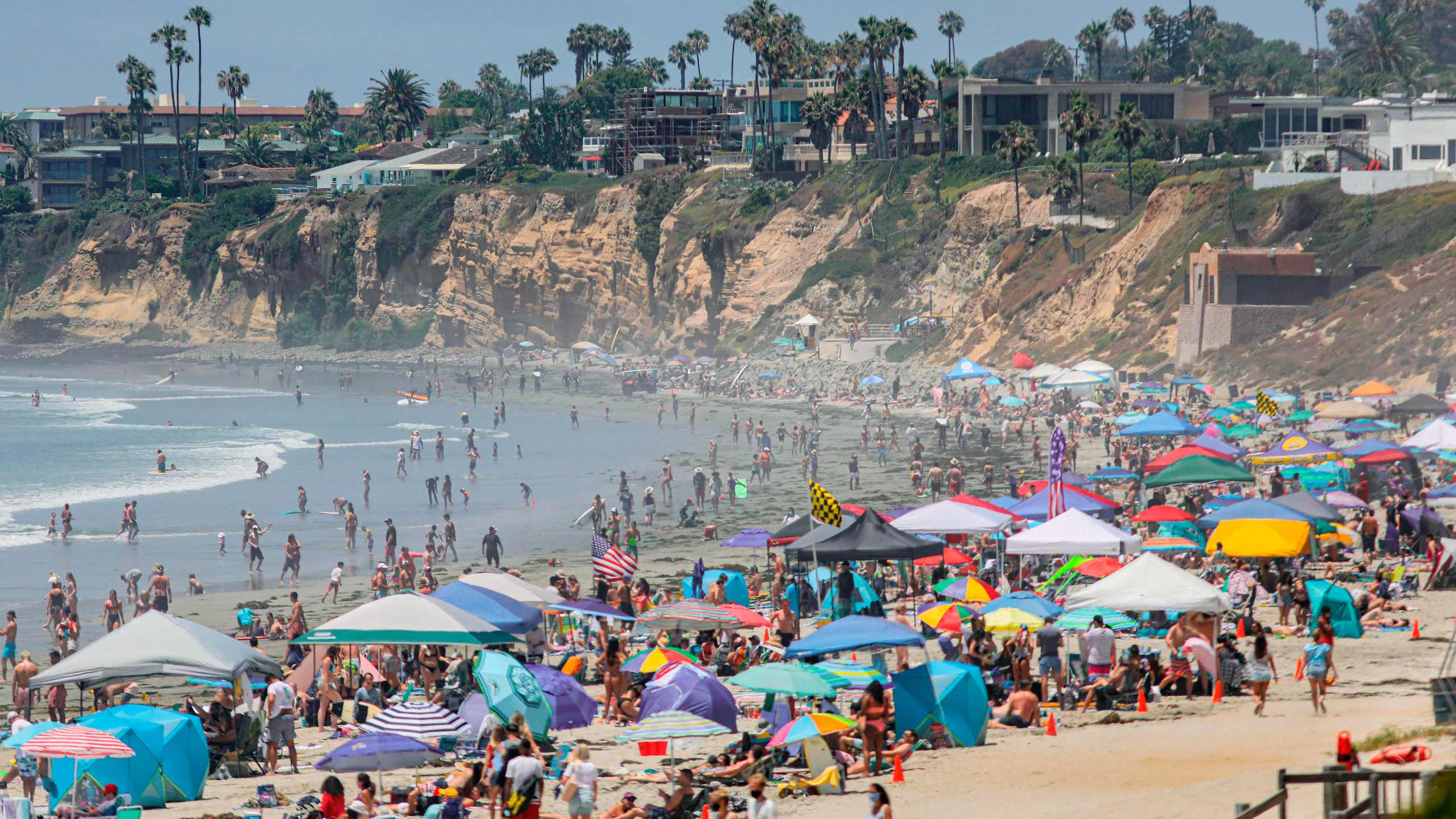 Beachgoers are seen along the shore in the Pacific Beach area of San Diego on July 4, 2020. (SANDY HUFFAKER/AFP via Getty Images)