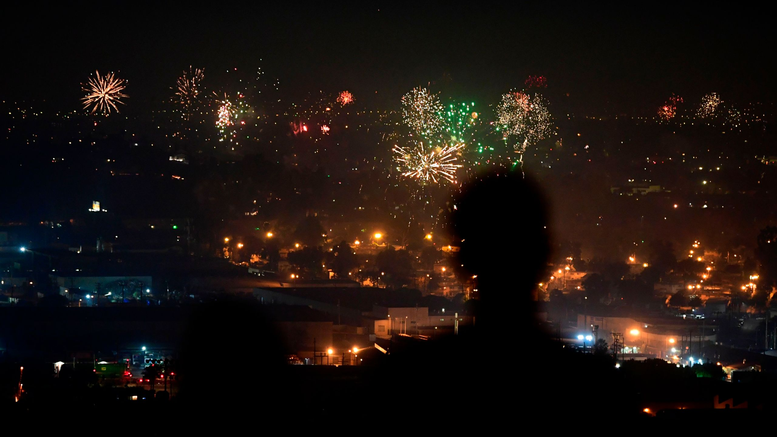 People watch fireworks burst over Los Angeles on July 4, 2020. (Frederic J. Brown / AFP / Getty Images)