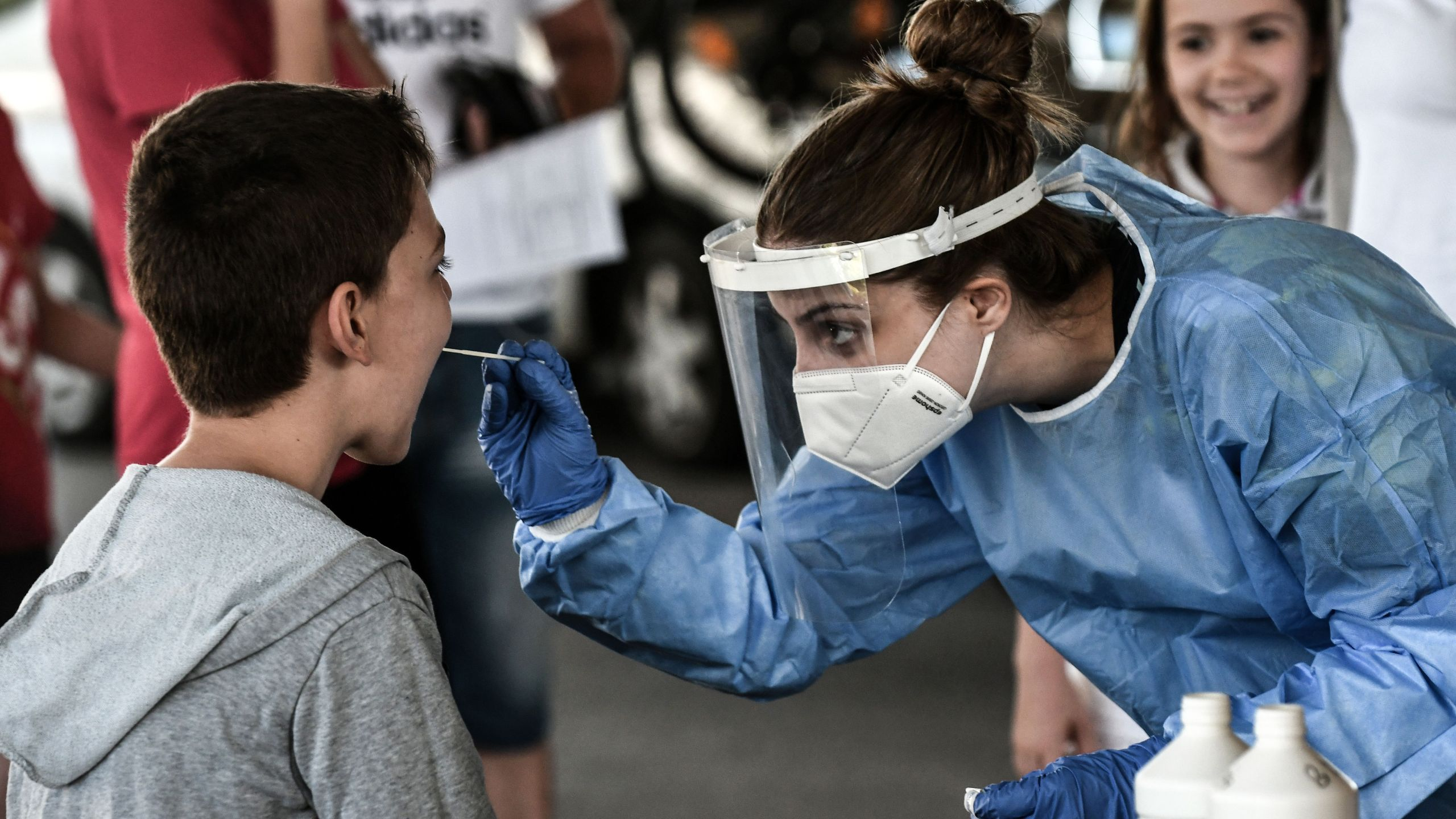 A public health worker collects a swab sample from a boy to test for the COVID-19 at the Greek-Bulgarian border crossing in Promachonas on July 10, 2020. (SAKIS MITROLIDIS/AFP via Getty Images)