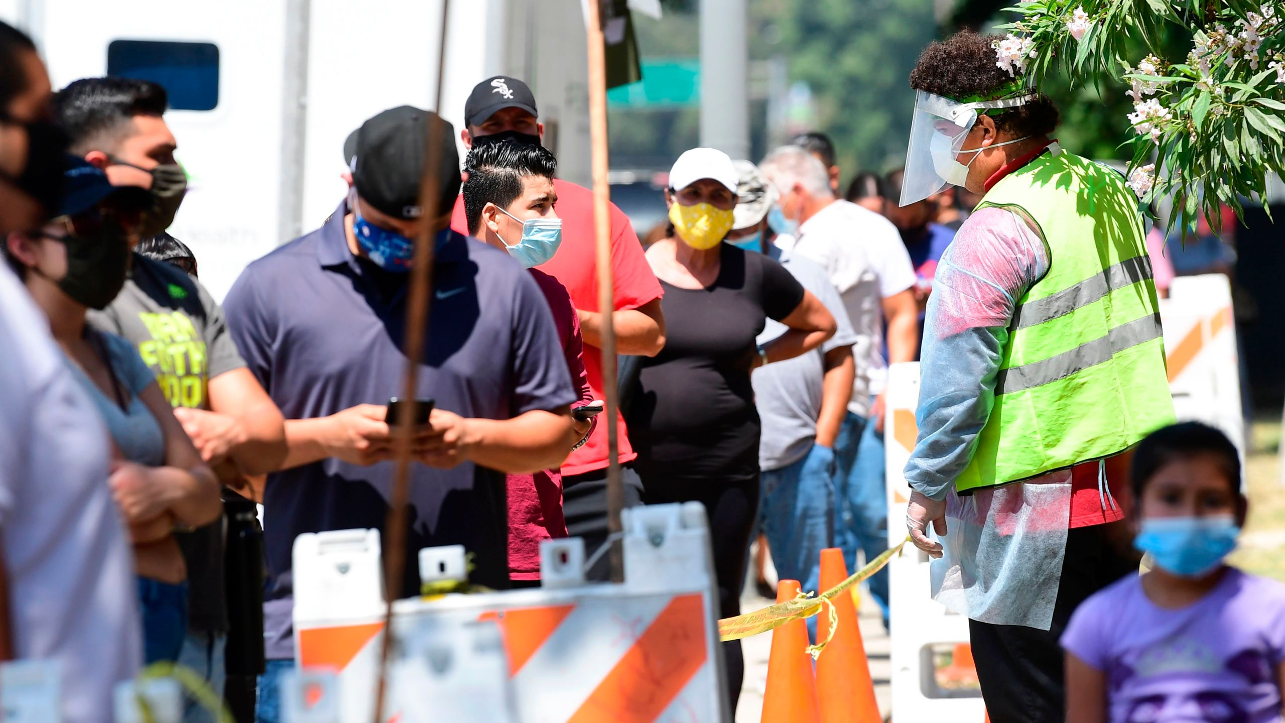A volunteer wearing personal protective equipment speaks with people waiting in line at a walk-in coronavirus test site in Los Angeles on July 10, 2020. (Frederic J. Brown / AFP / Getty Images)