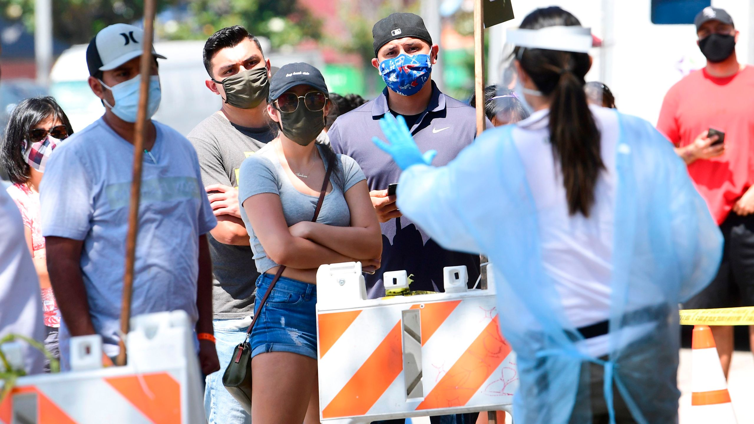 A COVID-19 test site volunteer gives directions to people waiting in line at a walk-in coronavirus test site in Los Angeles on July 10, 2020. (Frederic J. Brown / AFP / Getty Images)