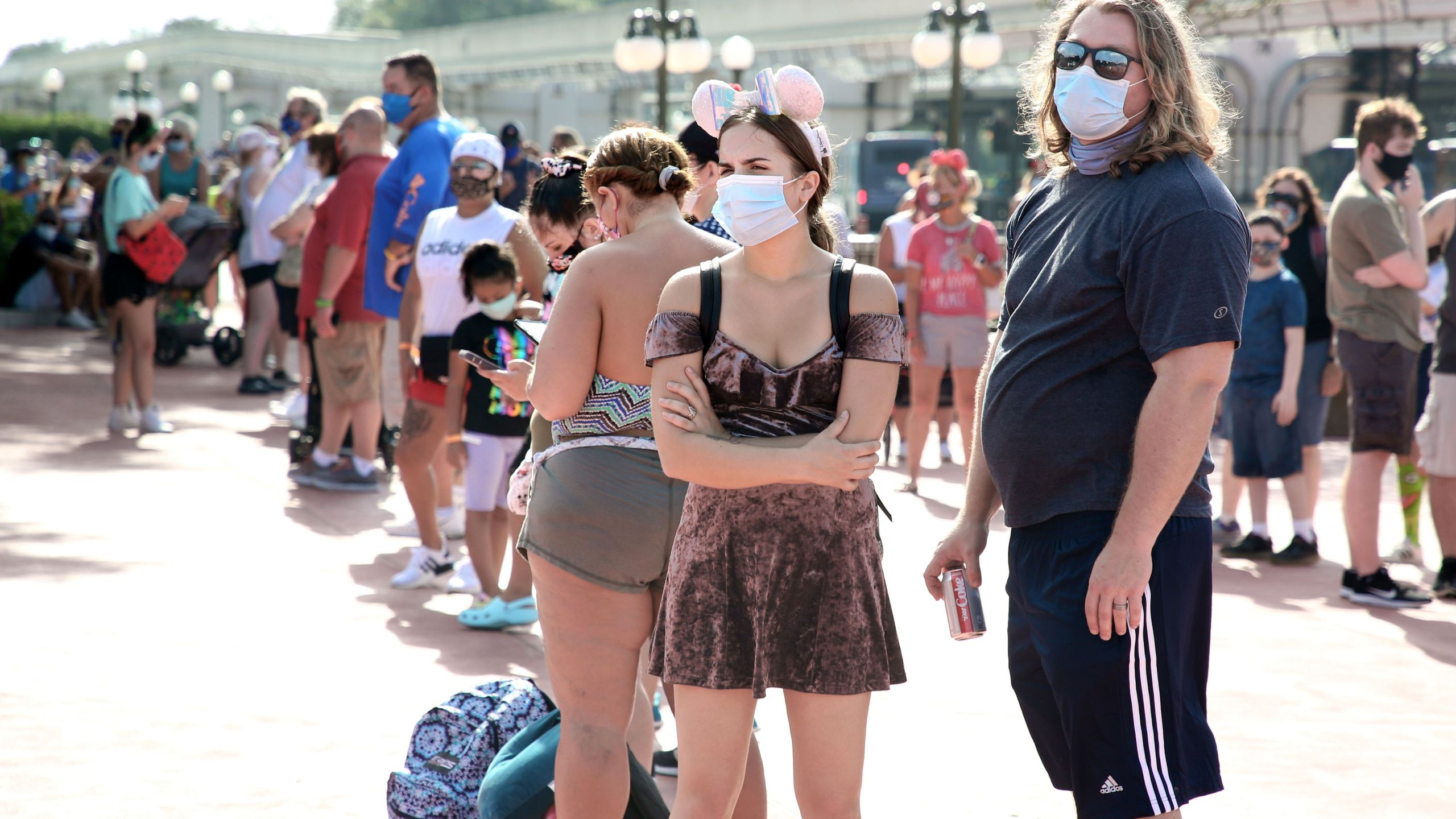 Guests wearing protective masks wait outside the Magic Kingdom theme park at Walt Disney World on the first day of reopening, in Orlando, Fla., on July 11, 2020. (Gregg Newton/AFP via Getty Images)