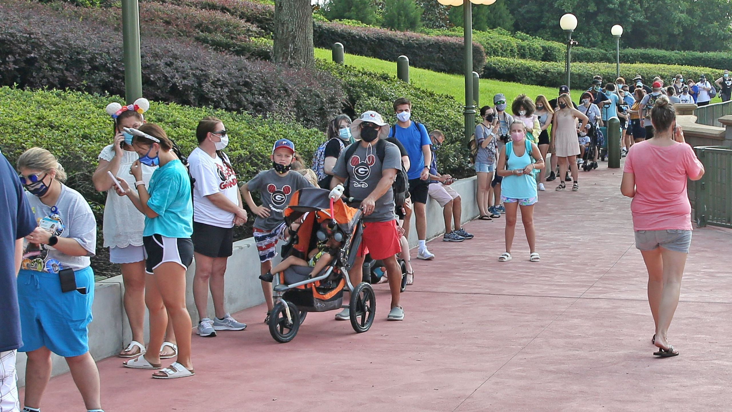 Guests wearing protective masks wait to pick up their tickets at the Magic Kingdom theme park at Walt Disney World on the first day of reopening, in Orlando, Florida, on July 11, 2020. (GREGG NEWTON/Gregg Newton/AFP via Getty Images)