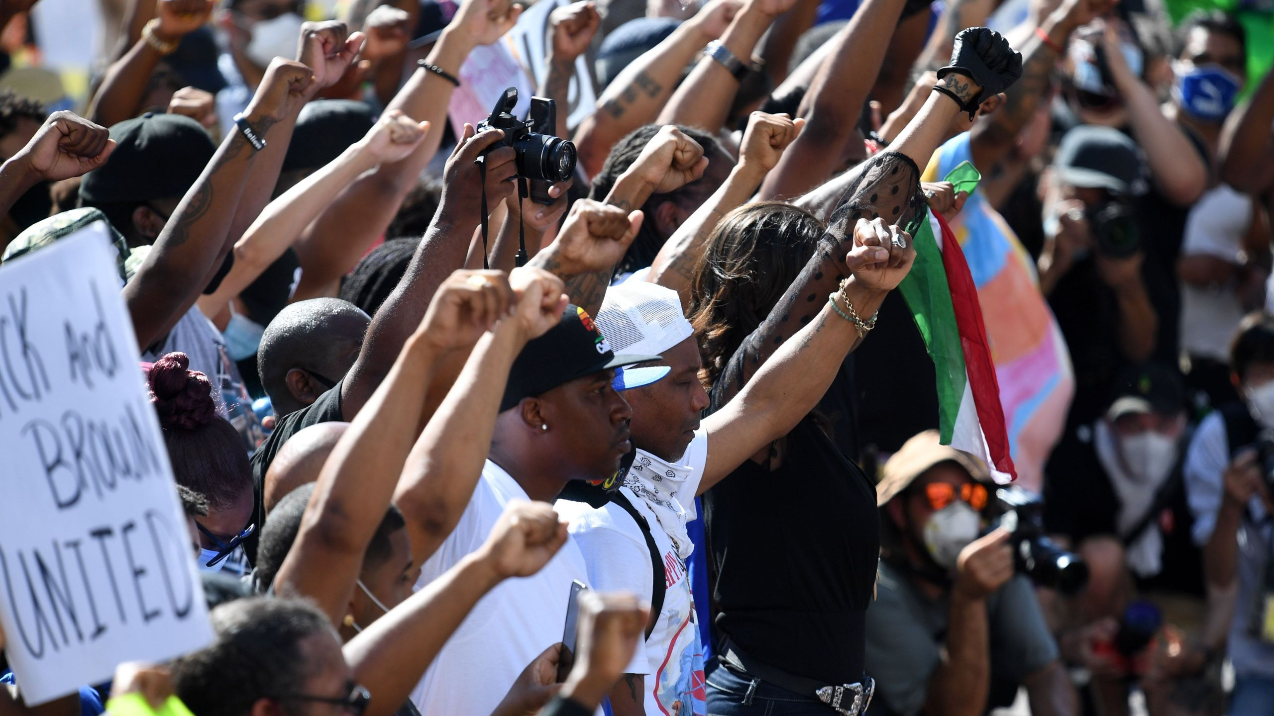 Activists and supporters of the Black and Brown Unity March raise their fists as the two groups march from different directions to meet in front of Los Angeles City Hall on July 12, 2020. (Robyn Beck / AFP / Getty Images)
