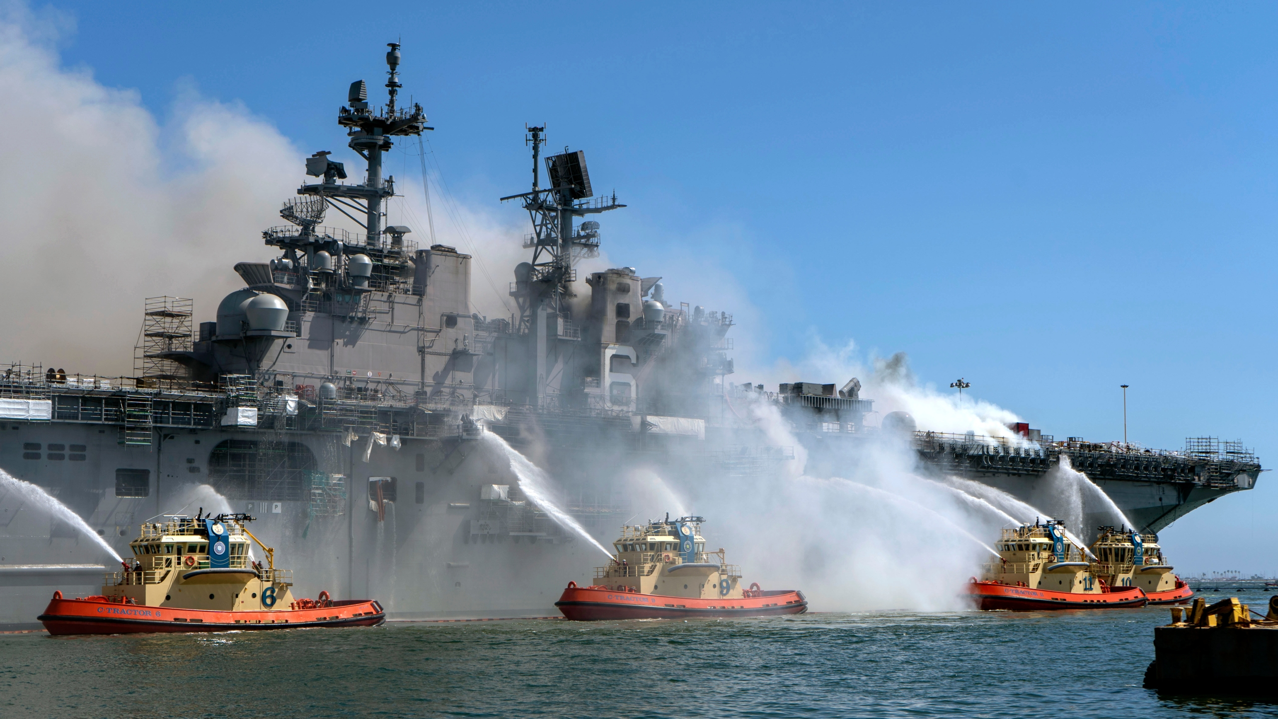 In this U.S. Navy released handout, sailors and federal firefighters combat a fire onboard USS Bonhomme Richard at Naval Base San Diego on July 12, 2020. (U.S. Navy photo by Mass Communication Specialist 3rd Class Christina Ross)