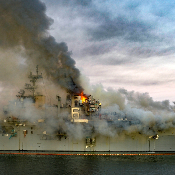 In this U.S. Navy released handout, a fire continues to be fought into the evening of July 12, 2020, on board USS Bonhomme Richard at Naval Base San Diego. (Mass Communication Specialist 2nd Class Austin Haist / U.S. Navy)