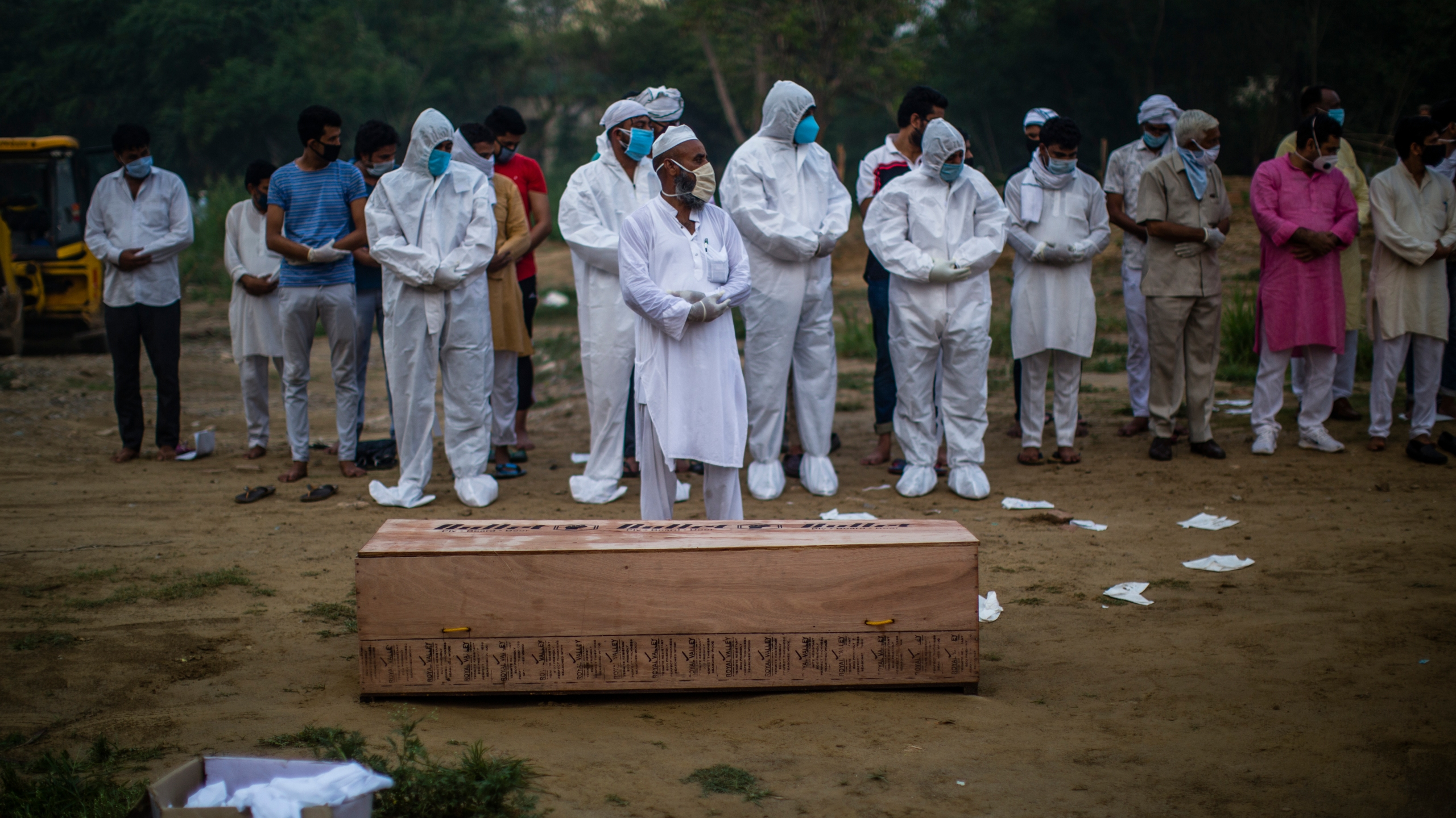 Relatives offer funeral prayers next to the coffin containing the body of a 35-year-old man who died from COVID-19 on July 17, 2020 in New Delhi, India. (Yawar Nazir/Getty Images)