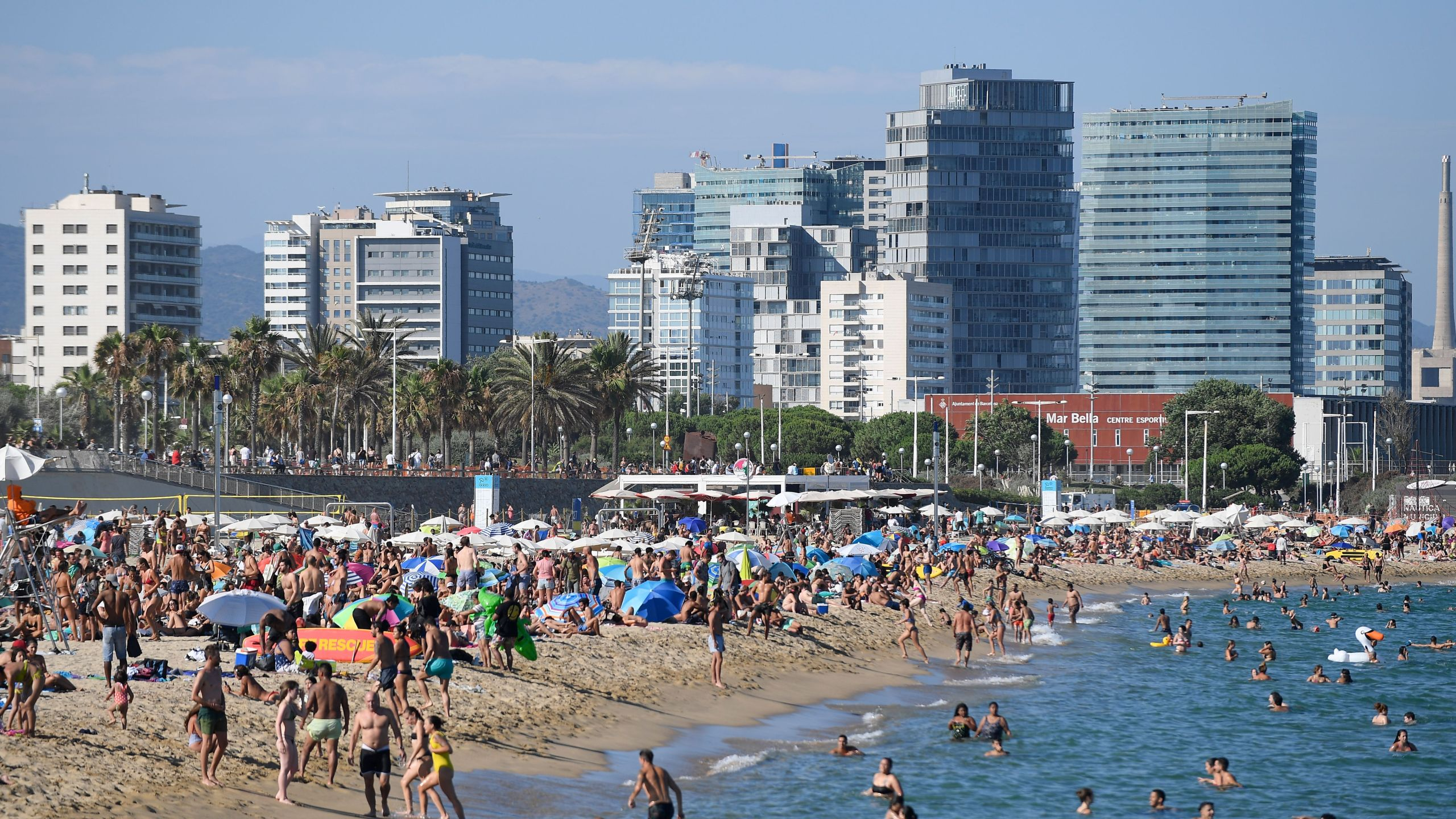 People swim and sunbathe at the Bogatell beach in Barcelona, one of the several sands of the city that have been closed on July 19, 2020, due to reaching the allowed capacity. (Josep LAGO / AFP via Getty Images)