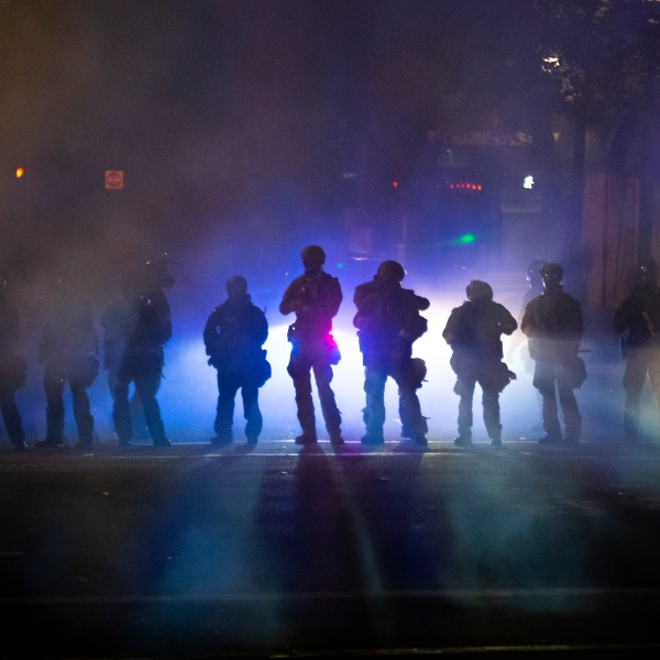 Federal officers walk through tear gas while dispersing a crowd of about a thousand people during a protest at a federal courthouse in Portland, Oregon, on July 21, 2020. (Nathan Howard / Getty Images)