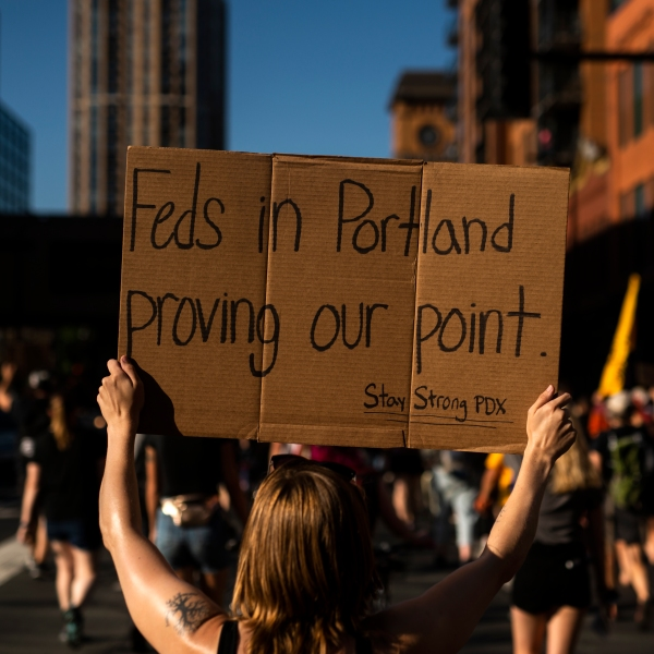 """A woman marches while holding a sign that says """"Feds in Portland proving our point"""" during a protest that started outside the Diana E. Murphy U.S. Courthouse in Minneapolis, Minnesota on July 23, 2020. (Stephen Maturen / Getty Images)"""