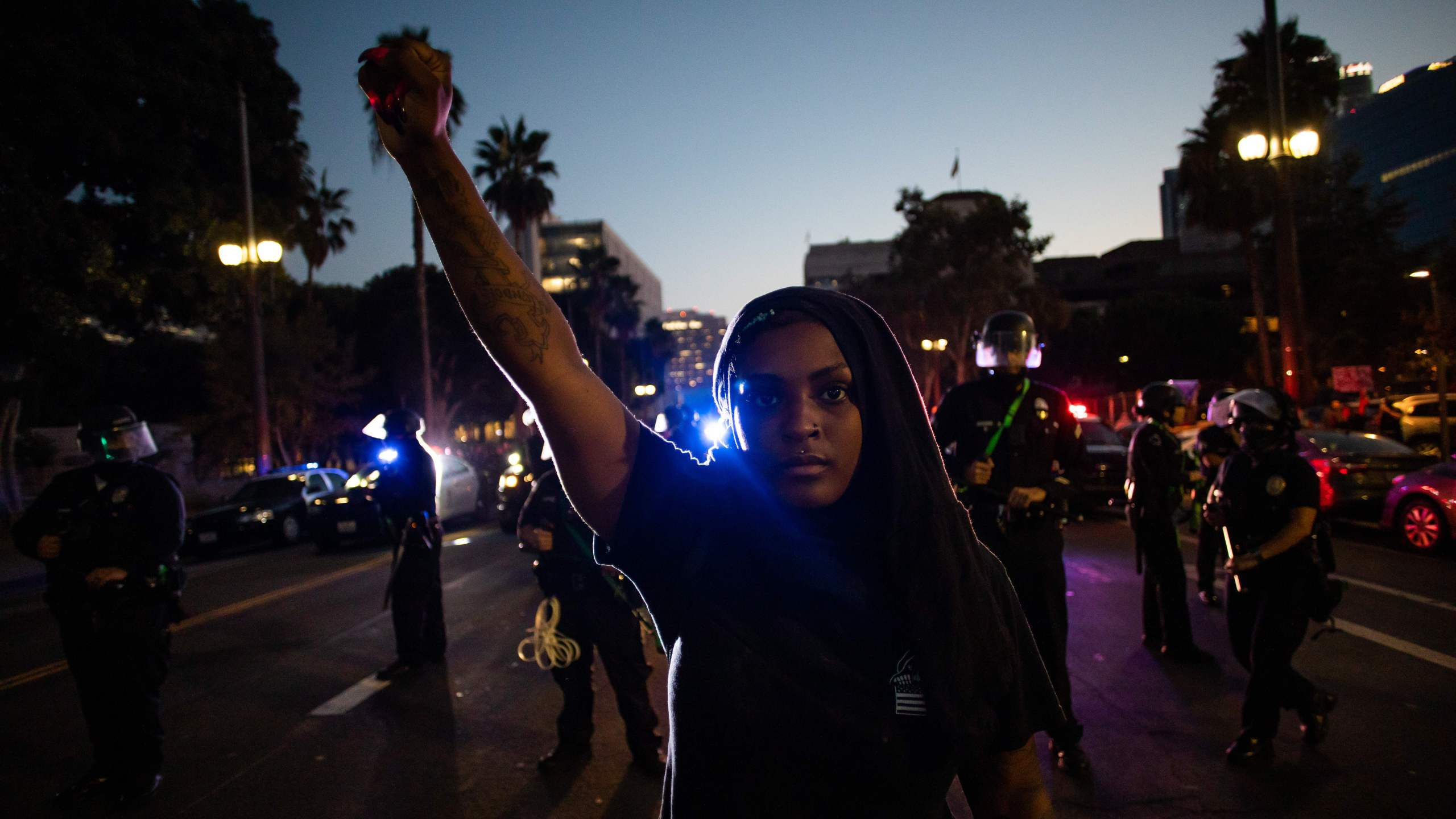 A woman holds up her fist in front of a row of police officers during a protest demanding justice for George Floyd, Breonna Taylor and also in solidarity with Portland's protests, in downtown Los Angeles, on July 25, 2020. (APU GOMES/AFP via Getty Images)