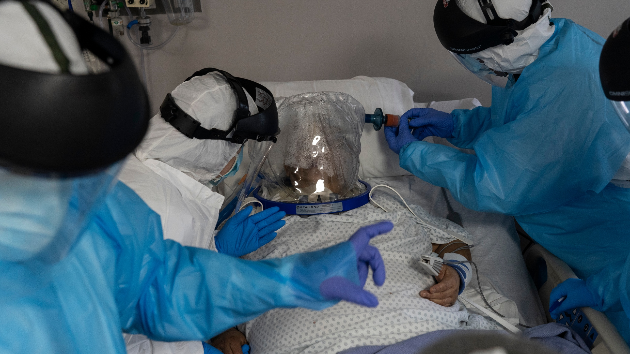 Medical workers treat a patient who is wearing a helmet-based ventilator in the COVID-19 intensive care unit at the United Memorial Medical Center on July 28, 2020 in Houston, Texas. COVID-19 cases and hospitalizations have spiked since Texas reopened, pushing intensive care units to full capacity and sparking concerns about a surge in fatalities as the virus spreads. (Go Nakamura/Getty Images)