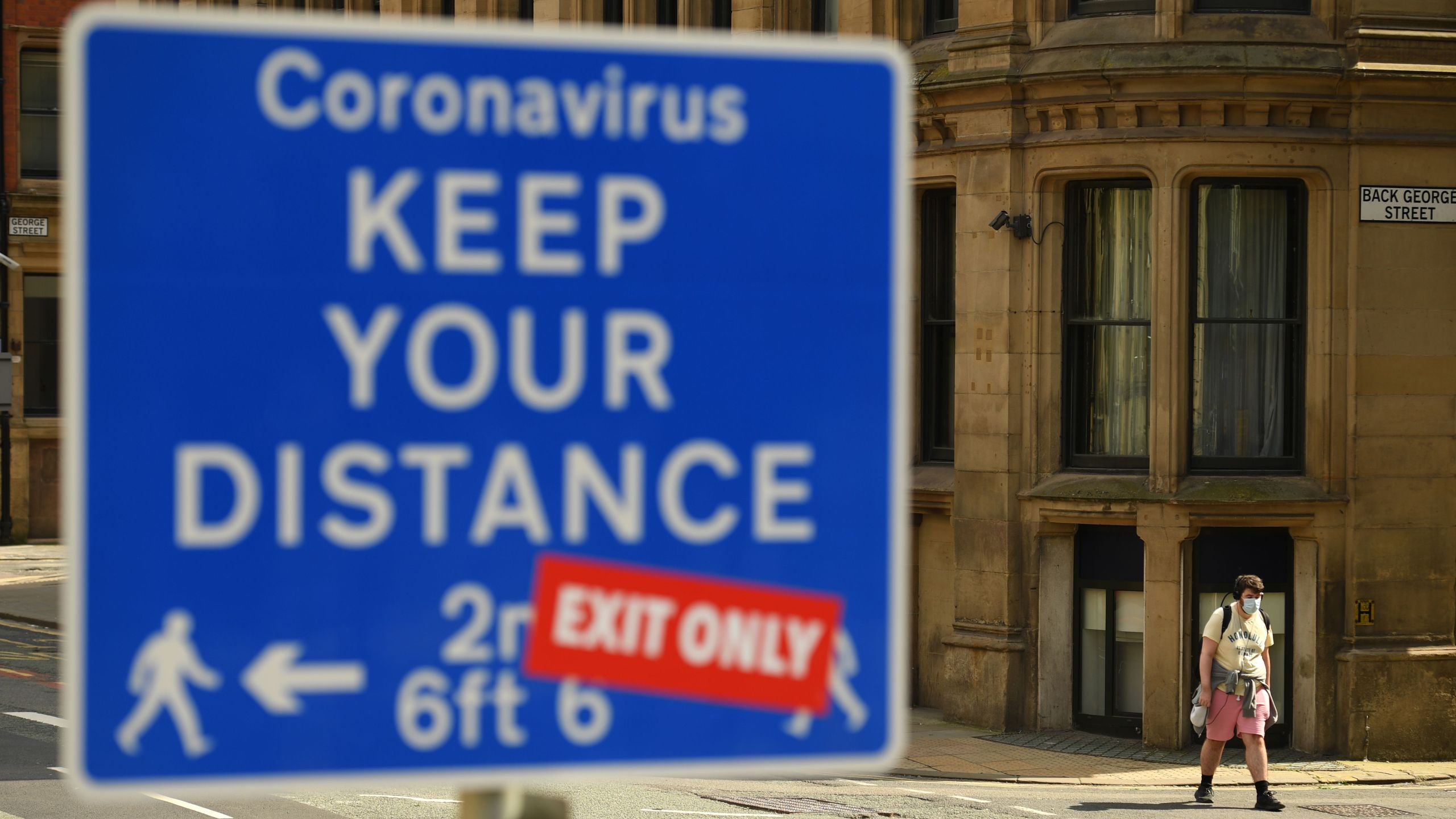 A sign requesting pedestrians to follow the governments social distancing guidelines is on view in the centre of Manchester, northwest England, on July 31, 2020. (Oli SCARFF / AFP) (Photo by OLI SCARFF/AFP via Getty Images)