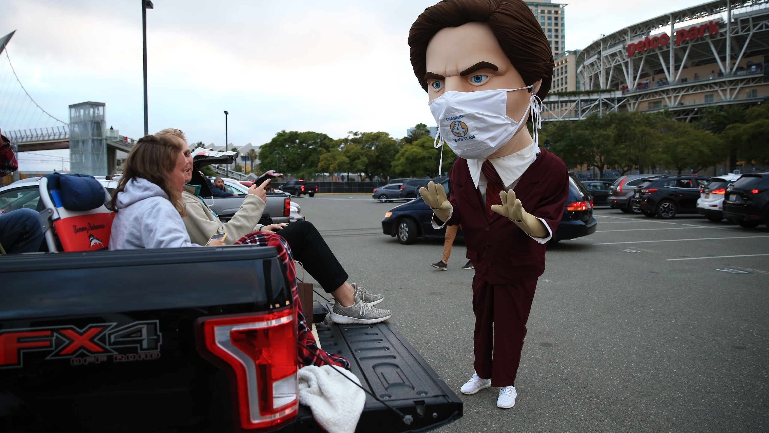 Fans of the San Diego Padres prepare to watch the movie Anchorman as they speak to a mascot of character Ron Burgundy outside of Petco Park at a drive-in movie on June 6, 2020, in San Diego. (Sean M. Haffey/Getty Images)