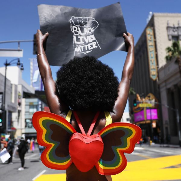 """A protester holds a """"Black Lives Matter"""" sign on Hollywood Boulevard during the All Black Lives Matter solidarity march, replacing the annual gay pride celebration, as protests continue in the wake of George Floyd's death on June 14, 2020. (Mario Tama/Getty Images)"""