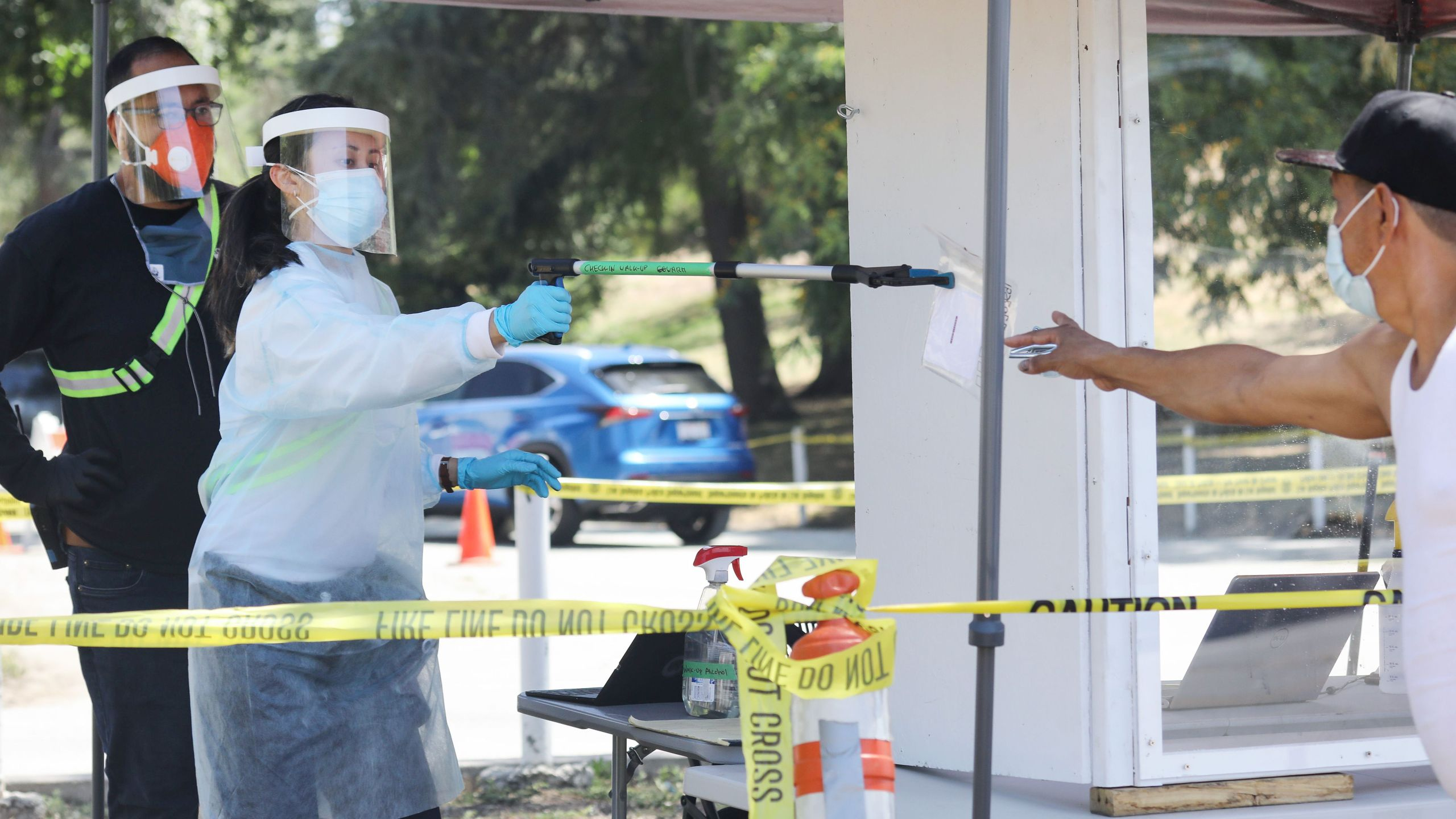 A worker dressed in personal protective equipment passes a biohazard bag containing a self-administered COVID-19 test to a man at a testing center at Lincoln Parkin Los Angeles amid the coronavirus pandemic on July 7, 2020. (Mario Tama/Getty Images)