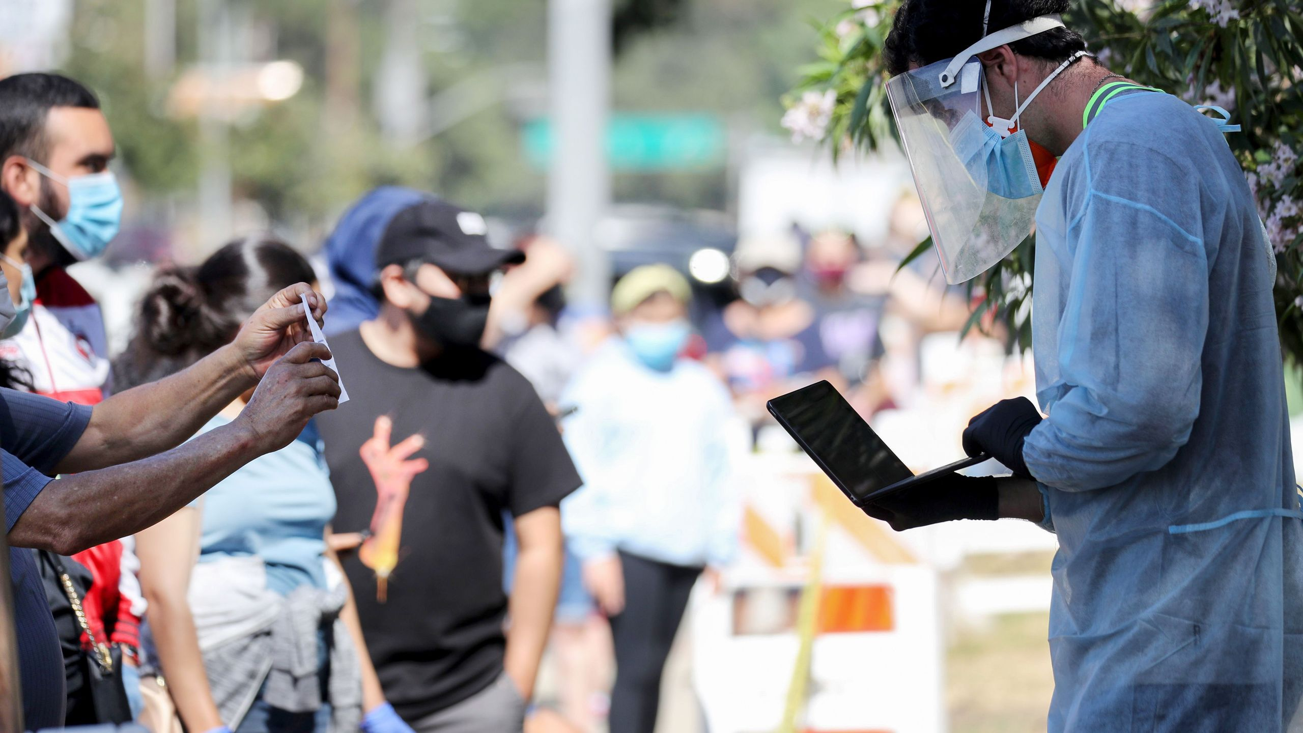 A testing associate dressed in personal protective equipment helps people waiting in line to check in at a COVID-19 testing center at Lincoln Park in Los Angeles on July 7, 2020. (Mario Tama / Getty Images)