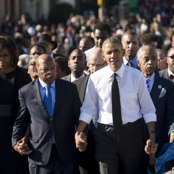 Barack Obama walks alongside Michele Obama and Rep. John Lewis across the Edmund Pettus Bridge to mark the 50th Anniversary of the Selma to Montgomery civil rights marches in Selma, Alabama, March 7, 2015. (SAUL LOEB/AFP via Getty Images)