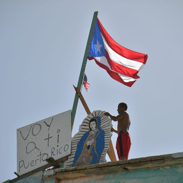 "A man places on his house next to a flag of Puerto Rico, a placard that read in Spanish ""Voy a ti Puerto Rico"" in Yabucoa on Sept. 28, 2017."