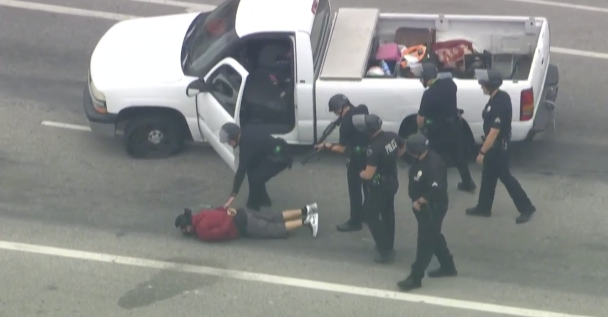 A pursuit suspect is detained by LAPD officers following a chase through North Hollywood on July 16, 2020. (KTLA)