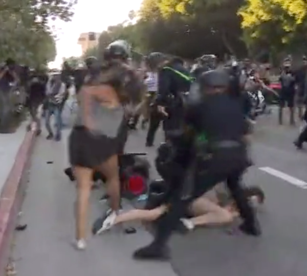 An LAPD officers holds a woman down and handcuffs her in downtown L.A. amid protests on July 25, 2020. (KTLA)