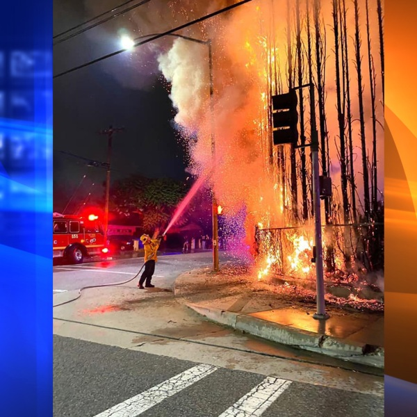 A firefighter is seen battling what appears to be a row of trees on fire on July 4, 2020. (Azusa PD Facebook)