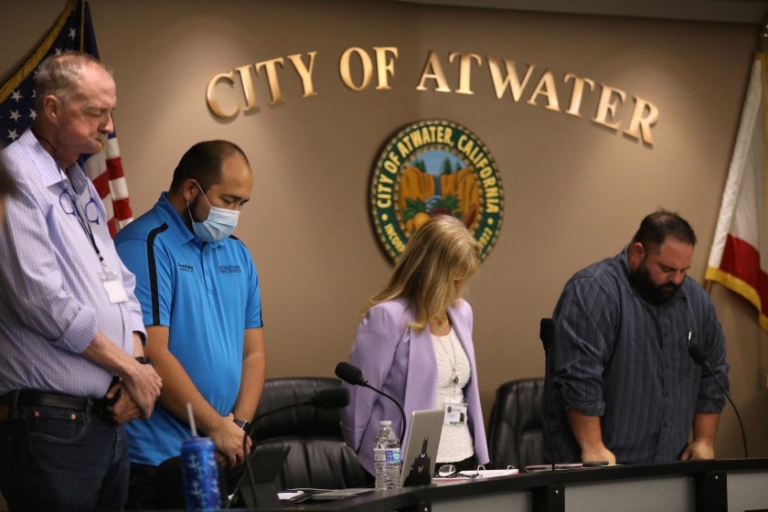 "Atwater, in California's Merced County, declared itself a ""sanctuary city"" from the state's coronavirus stay-at-home orders. City Council members John Cale, left, Danny Ambriz, City Manager Lori Waterman and Mayor Pro Tem Brian Raymond bow their heads during the invocation at the start of a meeting on May 26. (Genaro Molina / Los Angeles Times)"