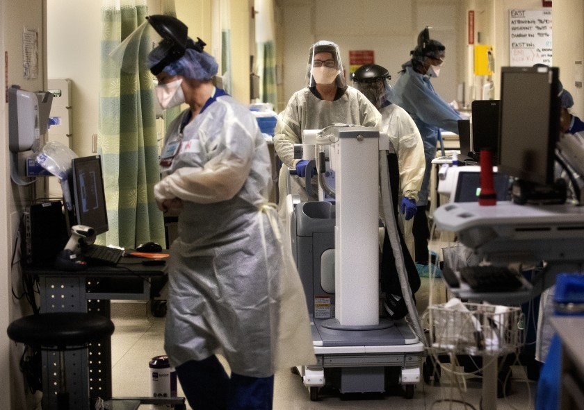Medical staffers work inside a COVID-19 isolation area at Los Angeles County-USC Medical Center. Medical teams from the Air Force arrived at the hospital, as well as Harbor-UCLA Medical Center, on Friday to offer support in critical care units.(Mel Melcon / Los Angeles Times)