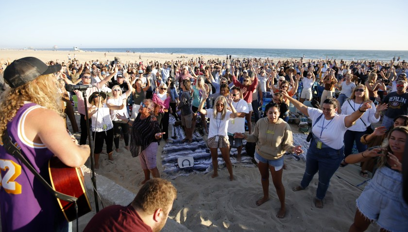 Hundreds gathered July 10 for the weekly Saturate OC worship event held north of the pier in Huntington Beach.(Raul Roa / Los Angeles Times)
