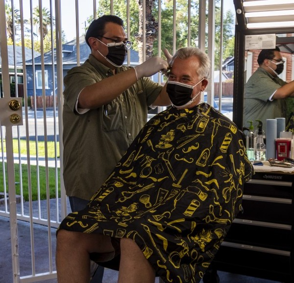 Obie Figueroa, owner of Obie's Barbershop & Shave in Riverside, cuts San Dimas resident Matt Nelson's hair Tuesday. The coronavirus pandemic has forced Figueroa to move his services outside.(Gina Ferazzi / Los Angeles Times)