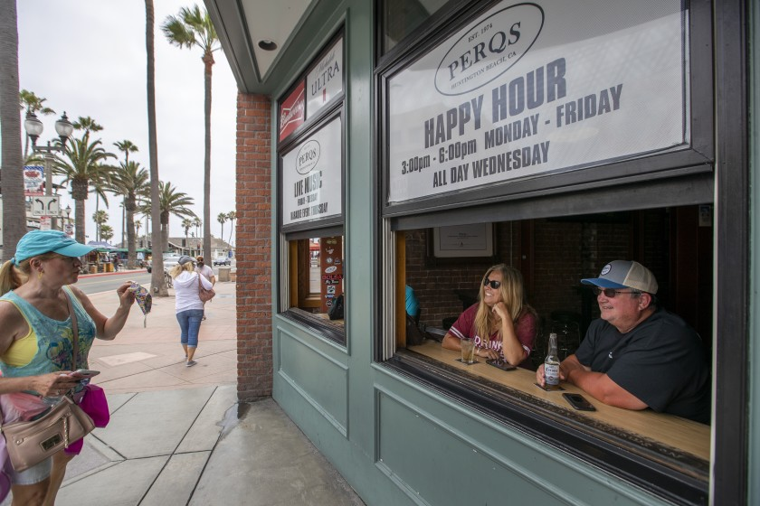 A couple enjoy drinks on Main Street in Huntington Beach on July 1 as they greet a passerby who says she can't get used to wearing a face mask.(Allen J. Schaben / Los Angeles Times)