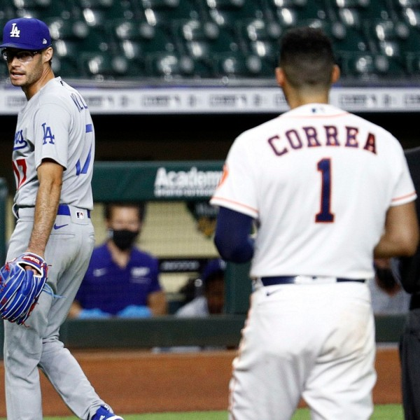 Joe Kelly of the Los Angeles Dodgers has a word with Carlos Correa of the Houston Astros as he walks off the mound after a series of high inside pitches in the sixth inning at Minute Maid Park on July 28, 2020 in Houston, Texas. Both benches emptied. (Bob Levey/Getty Images)