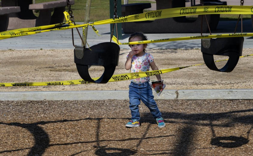 Adeline Hernandez, 2, of Riverside seems perplexed by the yellow caution tape as she approaches the closed off swing sets at Ryan Bonaminio Park during the COVID-19 pandemic in April 2020. (Gina Ferazzi / Los Angeles Times)
