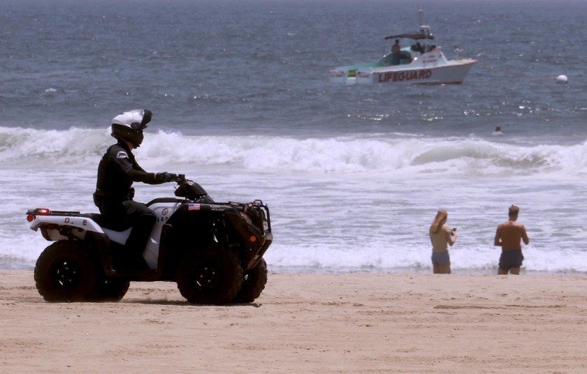 A police officer and a lifeguard boat patrol the shoreline in Venice Beach on July 5, 2020. Even though the beach was closed over the weekend, a few still made their way to the shore.(Genaro Molina / Los Angeles Times)