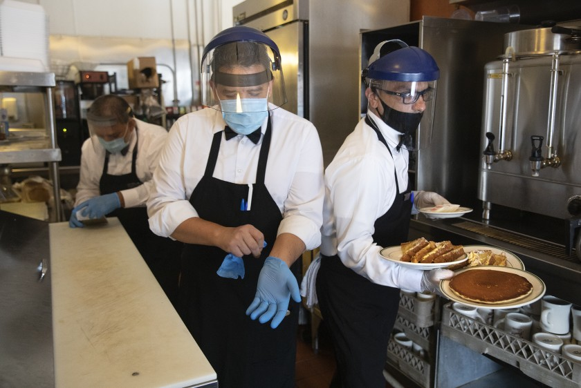 Waiter Jesus Segura, left, puts on gloves as waiter Alex Ortiz, passes by with breakfast plates for dine-in customers at rhe Original Pantry in downtown Los Angeles in this undated photo. (Mel Melcon / Los Angeles Times)