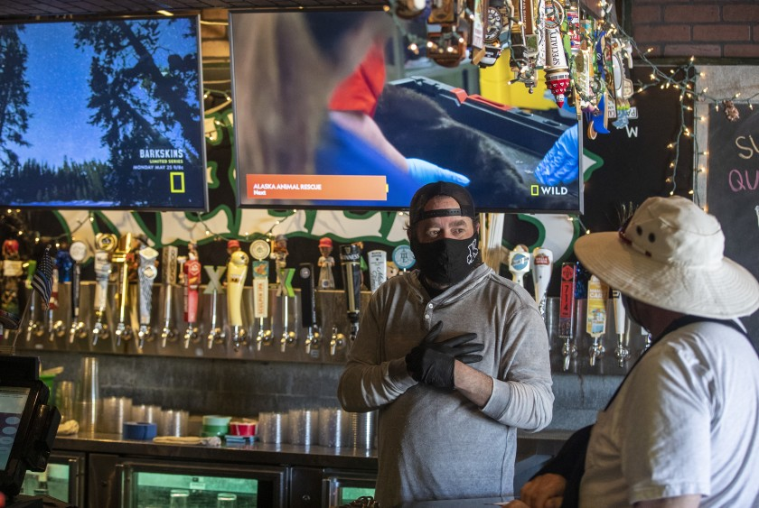 The owner of Kelly's Korner — one of Orange County's best-known sports bars — chats with a customer on May 16, 2020, in Placentia.(Brian van der Brug / Los Angeles Times)